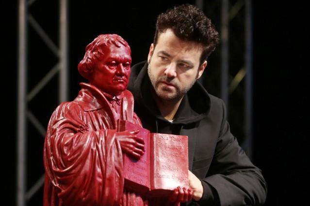 Der Darsteller von Martin Luther Frank Winkels mit einer Luther Figur des Kuenstlers Ottmar Hoerl