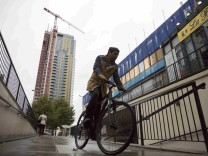 A man rides his bike past a view of the Elephant Park building development in Elephant and Castle south London, Britain