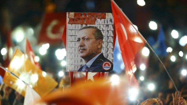 People wave flags and hold a portrait of Turkish President Erdogan as they wait for the arrival of Prime Minister Davutoglu in Ankara