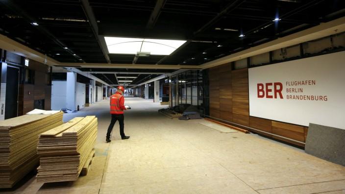 Aiport staff walk inside a terminal of Berlin Brandenburg international airport in Schoenefeld