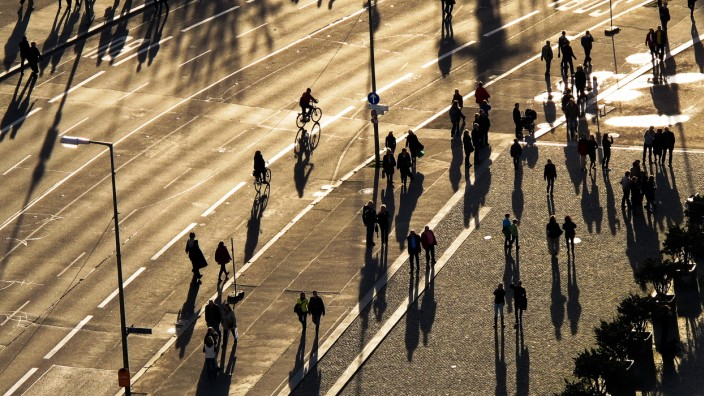 People cast long shadows as they walk along a street during warm and sunny weather in Berlin