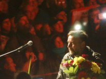Bachmann leader and founder of PEGIDA receives flowers from supporters during an anti-immigration rally in Dresden