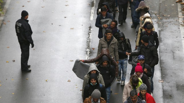 Migrants walk along street after passing Austrian-German border in Achleiten