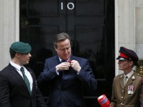 Britain's Prime Minister David Cameron attaches a poppy to his jacket to mark this year's Poppy Appeal at Number 10 Downing Street in central London