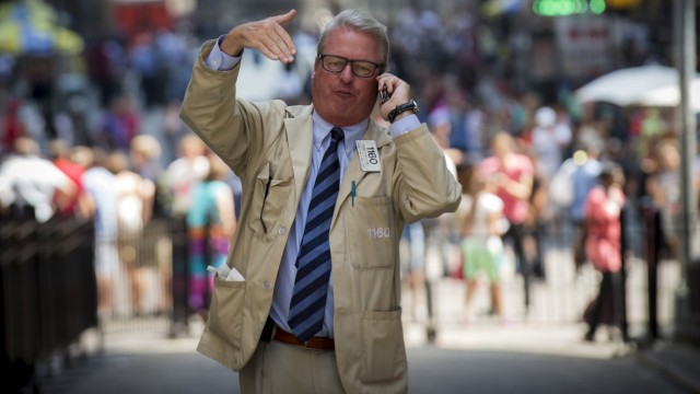 A trader talks on his phone outside the New York Stock Exchange on Wall St.