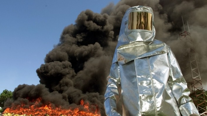 A FEDERAL POLICE WEARING AN ANTI-FIRE SUIT GUARDS THE BURNING OF COCAINE