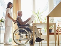 Germany Cologne Senior man reading newspaper in wheelchair caretaker standing beside model releas