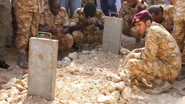 Qatari soldiers sit around the grave of their comrade, who was killed in Yemen, after his burial in Doha