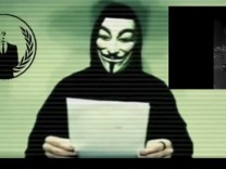 Still image taken from video released on social media shows a man wearing a mask associated with Anonymous making a statement