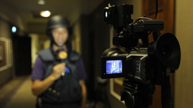 A television reporter speaks during a recording in the corridor at the Rixos hotel in Tripoli
