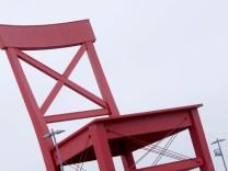 Schmuckbild 'Hochsitz'. Überdimensionierter Stuhl auf dem Parkplatz vor dem XXXLutz Aschheim
