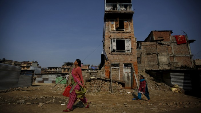 Women walk past houses that were damaged by an earthquake earlier this year, in Bhaktapur, Nepal
