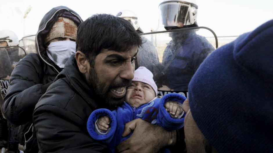 A stranded migrant holding a baby shouts next to a Greek police cordon following scuffles at the Greek-Macedonian border, near the village of Idomeni