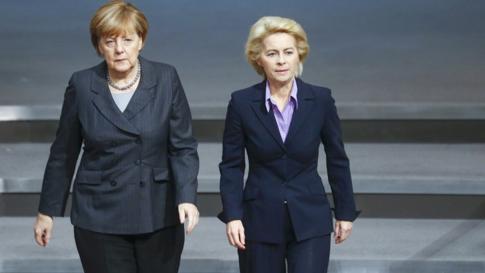 German Chancellor Merkel and Defence Minister von der Leyen walk during a session of the Bundestag, the German lower house of parliament, in Berlin