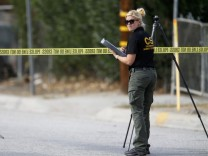 A Sheriff's Office Crime Scene Iinvestigator inspects the scene around an SUV where two suspects were shot by police following a mass shooting in San Bernardino