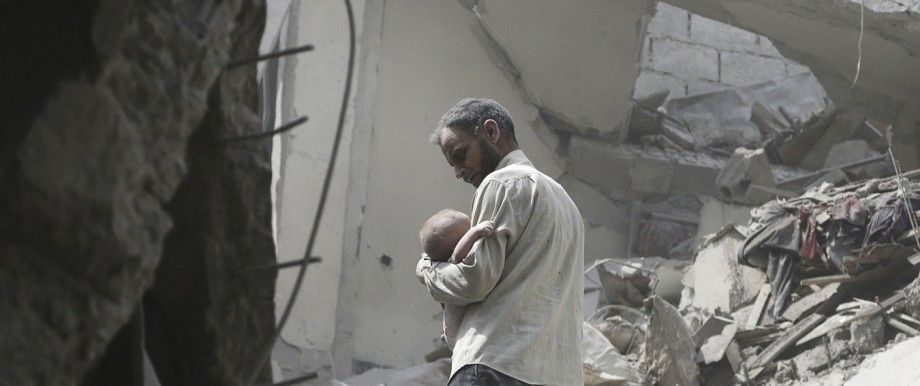 A man carries a child who survived what activists said were airstrikes by forces loyal to Syria's President Bashar al-Assad, in the Douma neighborhood of Damascus