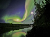 Swirls of green and red appear in an aurora over Whitehorse, Yukon