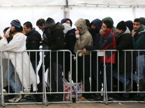 Migrants queue  inside a tent at the compound outside the Berlin Office of Health and Social Affairs waiting to register in Berlin