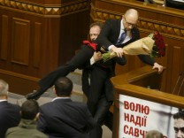 Rada deputy Barna removes PM Yatseniuk from the tribune, after presenting him a bouquet of roses, during the parliament session in Kiev