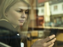 Germany Mannheim Young businesswoman in coffee shop checking mobile phone model released PUBLICAT; smartphone