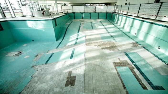 notwendige Maßnahmen im Hallenbad Ismaning. Fließen lösen sich vom Boden des großen Schwimmbeckens ab.