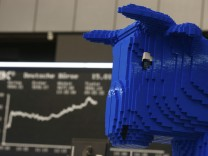 A bull figure made of LEGO bricks stands in front of the German share price index DAX board at the German stock exchange in Frankfurt