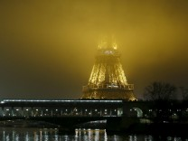 The Eiffel Tower is engulfed in fog early morning in Paris
