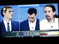 Two screens show three of the main candidates for Spain's national election at a live debate hosted by Spanish newspaper El Pais and Spanish PM Rajoy, who declined to attend that debate, at a simultaneous live interview at Telecinco TV in Madrid