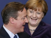 Britain's PM Cameron and Germany's Chancellor Merkel pose for a family photo during a EU leaders summit in Brussels