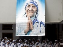 File photo of Catholic nuns from the order of the Missionaries of Charity gather under a picture of Mother Teresa in Kolkata