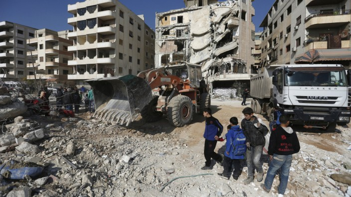 Boys inspect a site that was hit by an Israeli strike, killing a Lebanese militant leader Samir Qantar, in the Damascus district of Jaramana