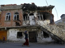 A woman walks past a building which was damaged during the security operations and clashes between Turkish security forces and Kurdish militants, in the southeastern town of Silvan in Diyarbakir province, Turkey
