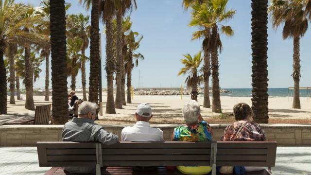 Rückansicht von Touristen die sich auf einer Bank ausruhen Ausblick auf Palmen und Strand Salou K
