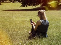 Woman sitting on a meadow of a park using smartphone model released Symbolfoto PUBLICATIONxINxGERxSU