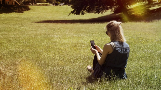 Woman sitting on a meadow of a park using smartphone model released Symbolfoto PUBLICATIONxINxGERxSU