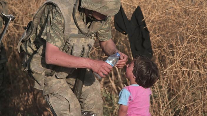 Ein türkischer Soldat bietet einem syrischem Flüchtlingskind Wasser an