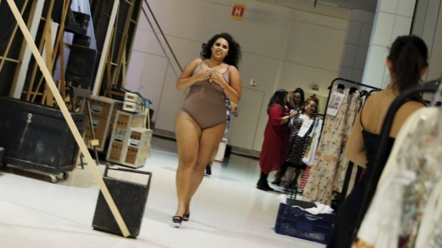 Model runs backstage before a presentation as part of Fashion Weekend Plus Size Summer 2015 collection show in Sao Paulo