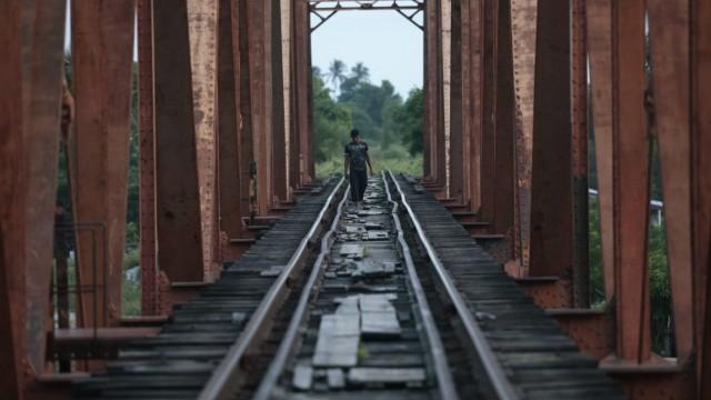 Central American migrant walks on the train tracks in Arriaga