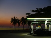 A worker prepares to fill a car at a gas station close to Copacabana beach in Rio de Janeiro