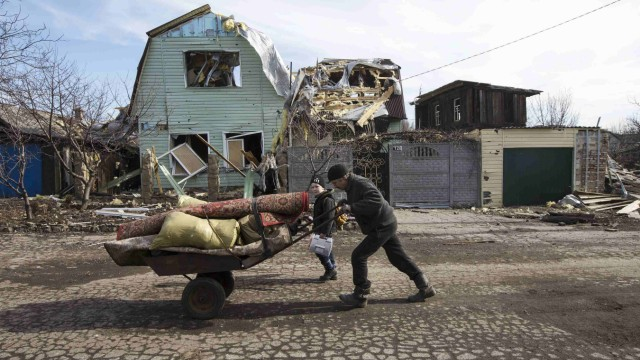 A man pushes a wheelbarrow past a house damaged by fighting in the town of Debaltseve