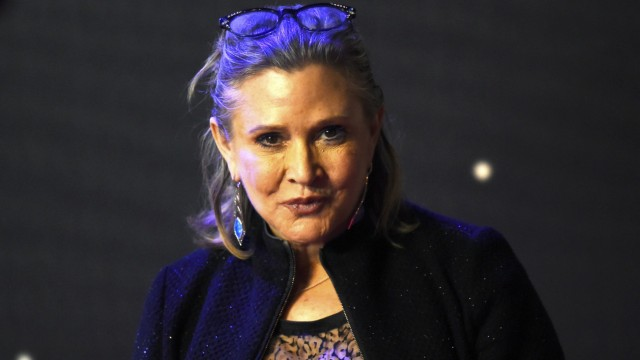 Carrie Fisher  poses for cameras as she arrives at the European Premiere of Star Wars, The Force Awakens in Leicester Square, London