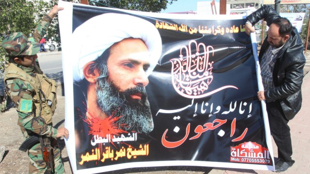 Iraqi men hold a banner of Shi'ite cleric Nimr al-Nimr, as they prepare to hang it in a street in Basra