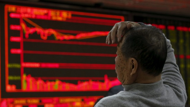 A man looks at an electronic board showing stock information at a brokerage house in Beijing