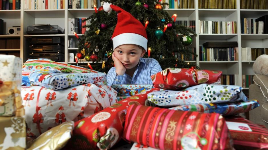 Weihnachten Kleiner Junge model released mit Weihnachtsmannmütze vor einem geschmückten Tannenbau; Geschenke