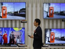 An employee uses his mobile phone in front of LG Electronics' organic light-emitting diode TV sets, which are made with LG Display flat screens, at its store in Seoul