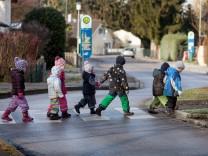 Kinder überqueren Zebrastreifen auf der Dorfstraße in Ismaning