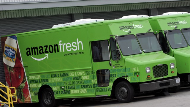 Amazon Fresh delivery vans are parked at an Amazon Fresh warehouse in Inglewood