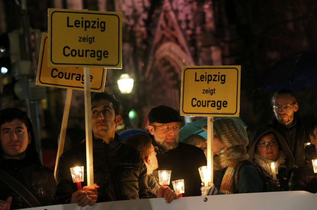 Participants hold candles and posters reading 'Lepizig shows courage' during a protest against LEGIDA, the Leipzig arm of the anti-Islam movement PEGIDA, in front of St. Nicholas Church in Leipzig