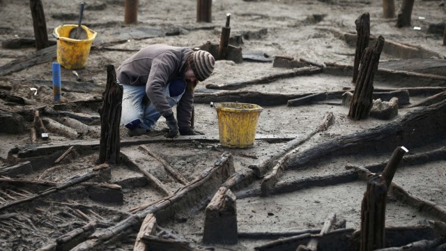 An archaeologist from the University of Cambridge Archaeological Unit, uncovers Bronze Age wooden houses, preserved in silt, from a quarry near Peterborough