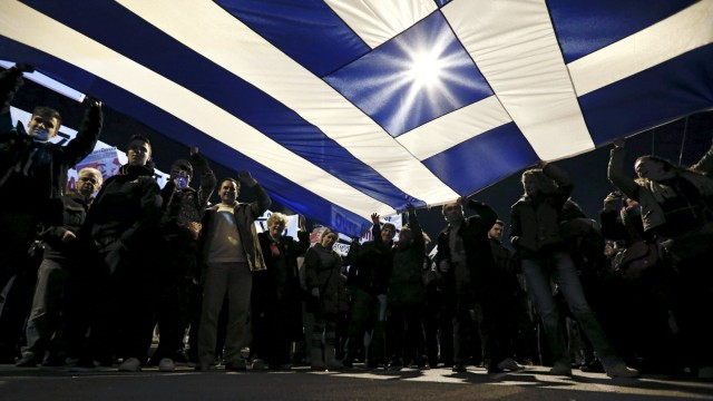 File photo of protesters holding a giant Greek national flag during an anti-austerity and pro-government demonstration in front of the parliament in Athens